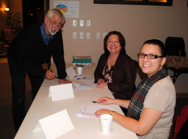 Resident Brian Sawyer is greeted and checked in by Community Manger Alina Cochran and assistant Sandra Bigas.